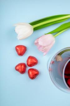 Vista superior de tulipanes de color blanco y rosa con una copa de vino y caramelos de chocolate en forma de corazón en papel rojo esparcidos sobre la mesa azul