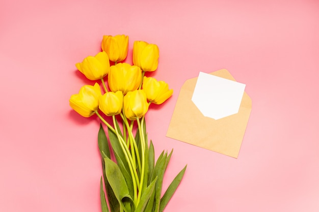 Vista superior de tulipanes rojos y envoltura artesanal con una letra, en posición plana,