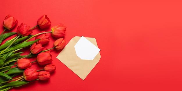Vista superior de tulipanes rojos y sobre de artesanía con una carta