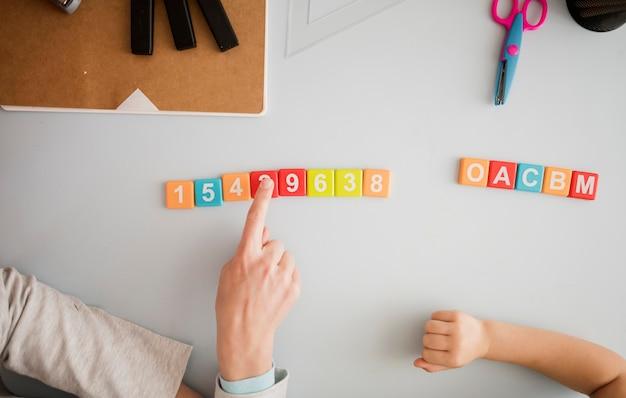 Vista superior del tutor enseñando al niño en el escritorio sobre números y letras