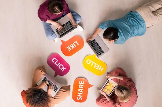 Vista superior de los usuarios de internet que utilizan dispositivos modernos mientras interactúan en línea, etiquetas coloridas de me gusta, hola, compartir, haga clic en el piso