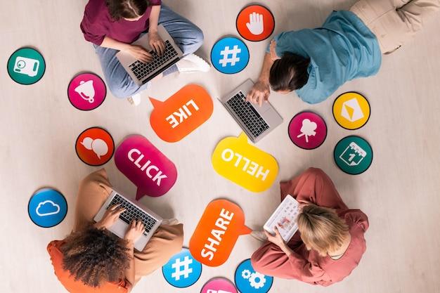 Vista superior de los usuarios de internet sentados en círculo entre las etiquetas e iconos de actividad de las redes sociales y navegando por la red en los dispositivos