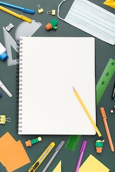Vista superior de útiles escolares con cuaderno y lápices