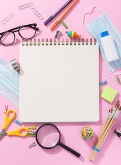 Vista superior de útiles escolares con cuaderno y lupa