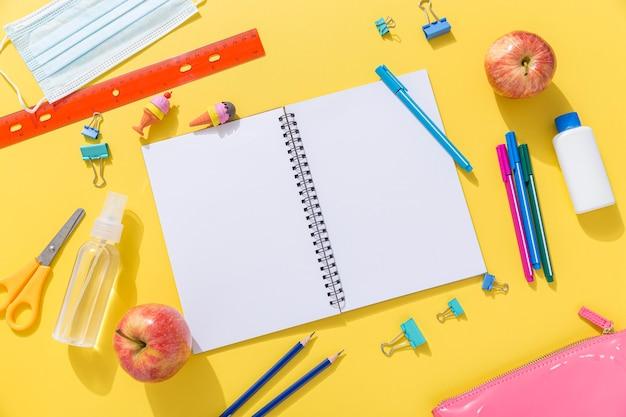 Vista superior de útiles escolares con cuaderno y manzanas