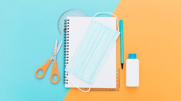 Vista superior de útiles escolares con cuaderno y máscara médica
