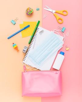 Vista superior de útiles escolares con cuaderno y mascarilla