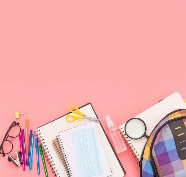 Vista superior de útiles escolares con cuadernos y mochila