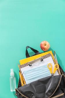Vista superior de útiles escolares con espacio de copia y mochila