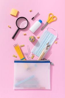 Vista superior de útiles escolares con lupa y tijeras