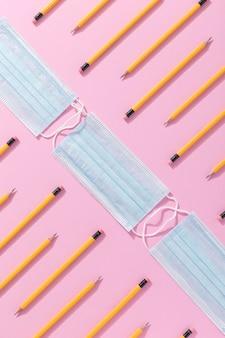 Vista superior de útiles escolares con mascarilla y lápices