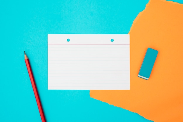 Vista superior de útiles escolares y papel de tarjeta sobre fondo turquesa