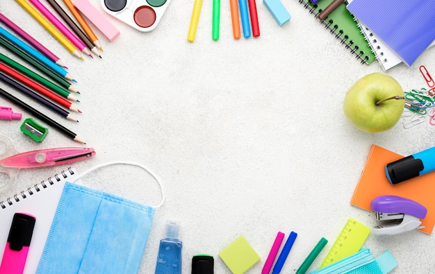Vista superior de útiles escolares para el regreso a la escuela con lápices y manzana