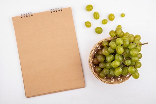 Vista superior de uva blanca en canasta y bloc de notas sobre fondo blanco con espacio de copia