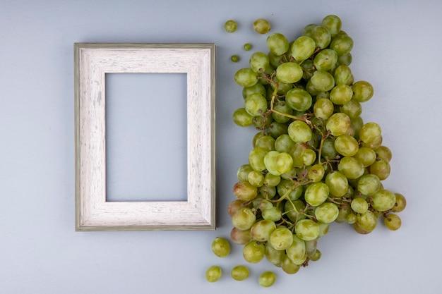 Vista superior de uva blanca y marco sobre fondo gris con espacio de copia