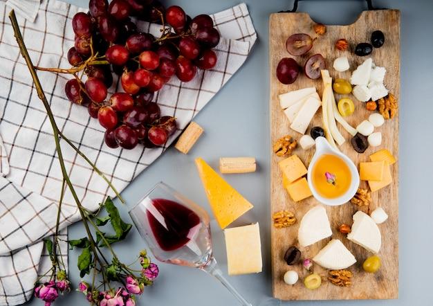Vista superior de uva y flores sobre tela con queso mantequilla de nueces de oliva en la tabla de cortar y un vaso de corchos de vino en blanco
