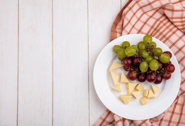 Vista superior de uva y queso en rodajas en placa sobre tela escocesa sobre fondo de madera con espacio de copia