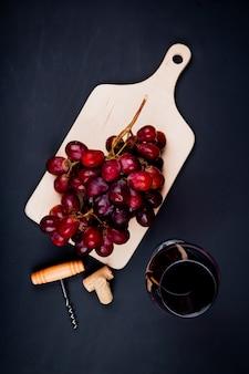 Vista superior de uva en tabla de cortar con vino tinto en vidrio y corchos con sacacorchos en mesa negra