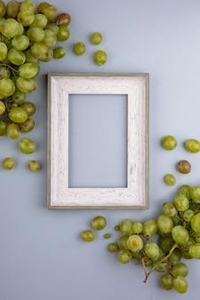 Vista superior de uvas blancas y marco sobre fondo gris con espacio de copia
