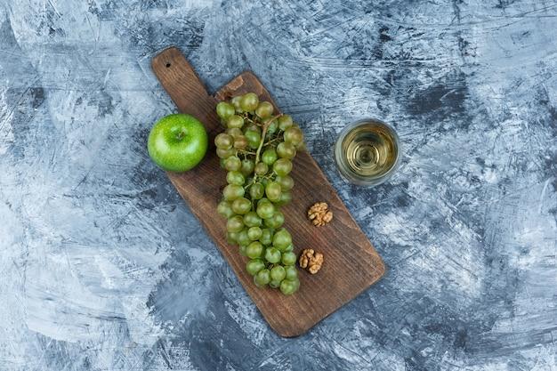 Vista superior de uvas blancas, nueces, manzana en tabla de cortar con vaso de whisky sobre fondo de mármol azul oscuro. horizontal