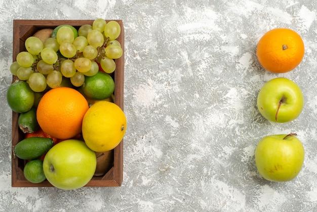 Vista superior de uvas frescas con manzanas feijoa y mandarinas sobre fondo blanco fruta cítrica exótica fresca madura suave