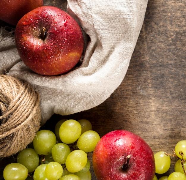 Vista superior de uvas de otoño y manzanas con cuerda