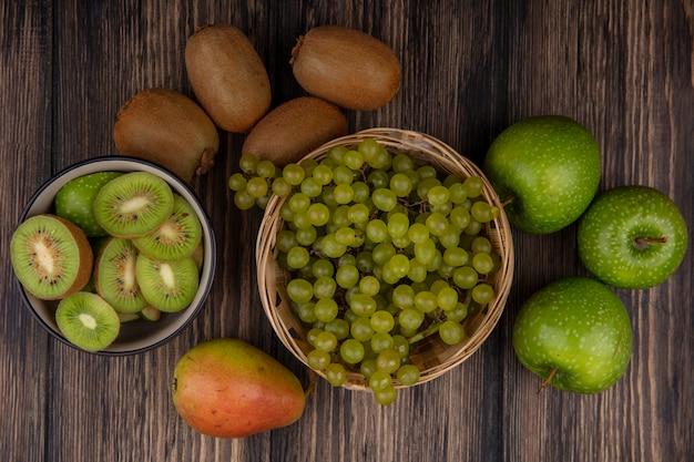 Vista superior de uvas verdes en una canasta con manzanas verdes y kiwi con rodajas en un recipiente sobre un fondo de madera