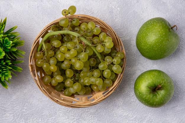 Vista superior de uvas verdes en una canasta con manzanas verdes sobre un fondo blanco.