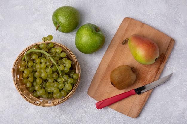 Vista superior de uvas verdes en una canasta con pera kiwi y cuchillo sobre una tabla de cortar con manzanas verdes sobre un fondo blanco.