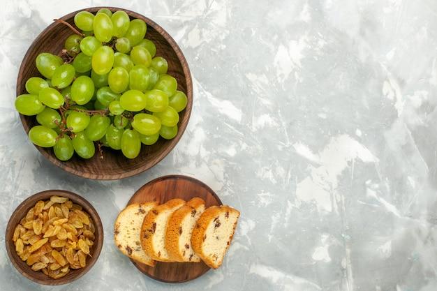 Vista superior de uvas verdes frescas suaves y deliciosas con tortas en un escritorio blanco claro