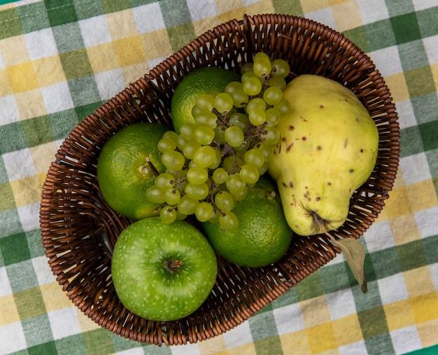 Vista superior de uvas verdes con manzana verde, mandarinas y pera en una canasta sobre una toalla a cuadros verde-amarillo