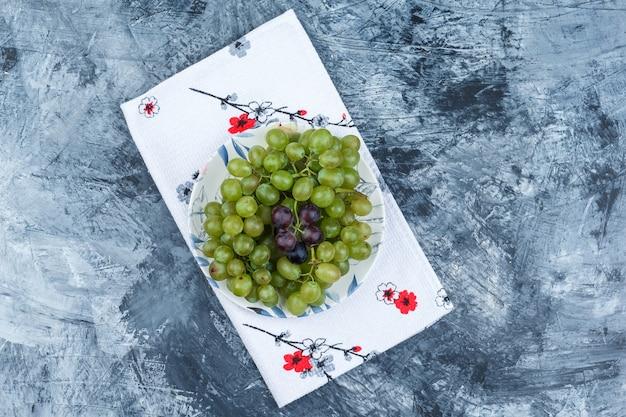 Vista superior de uvas verdes en placa sobre yeso sucio y fondo de toalla de cocina. horizontal