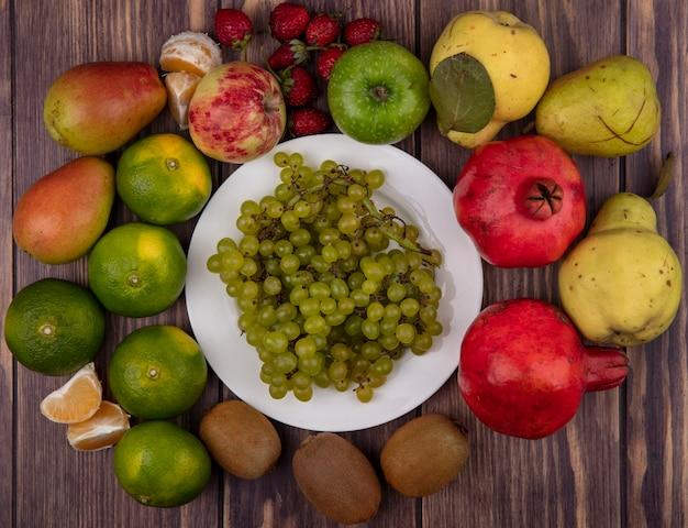 Vista superior de uvas verdes en un plato con kiwi mandarinas peras fresas y granadas en una pared de madera
