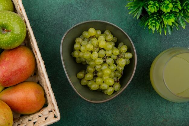 Vista superior de uvas verdes en un recipiente con una manzana verde y peras en una canasta con jugo sobre un fondo verde