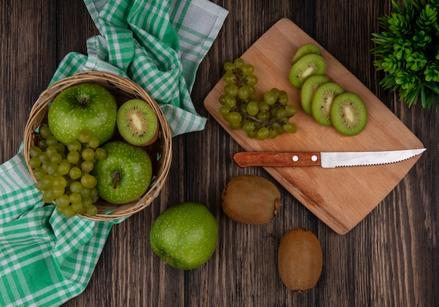 Vista superior de uvas verdes con rodajas de kiwi y un cuchillo en una tabla y manzanas verdes en una canasta sobre una toalla a cuadros verde sobre un fondo de madera