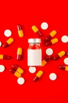 Vista superior de la vacuna covid dentro de un pequeño matraz con pastillas sobre fondo rojo.