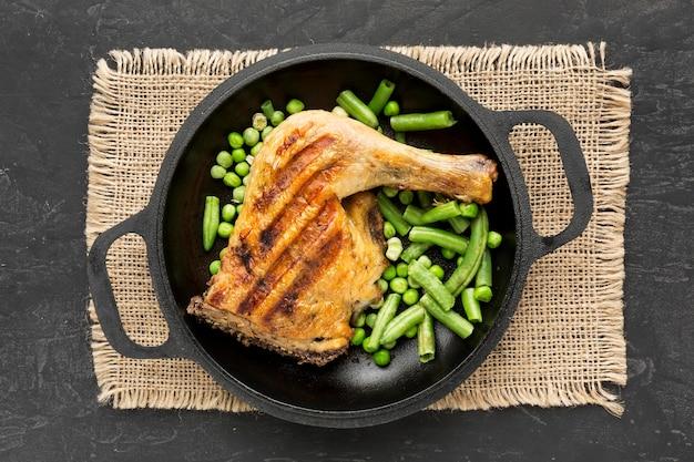 Vista superior de vainas de pollo y guisantes al horno en sartén