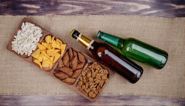 Vista superior de variados aperitivos de cerveza, galletas saladas, papas fritas y semillas de girasol en una bandeja de madera con botellas de cerveza en tela de saco rústico