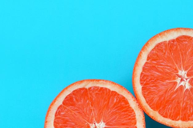Vista superior de varias rodajas de pomelo sobre fondo brillante en color azul