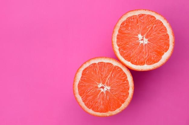 Vista superior de varias rodajas de pomelo sobre fondo brillante en color rosa
