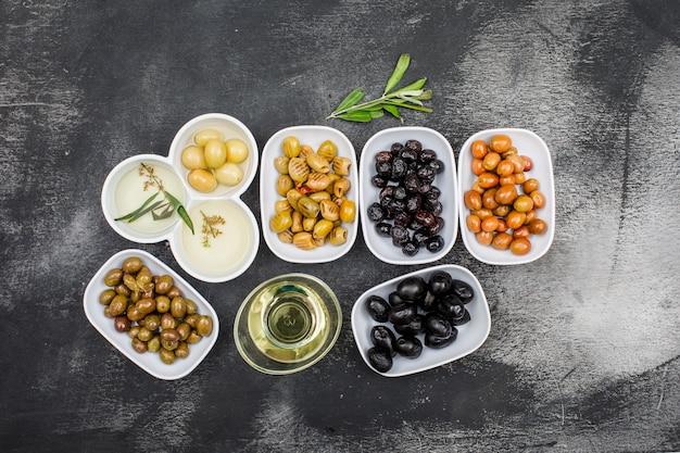 Vista superior una variedad de aceitunas y aceite de oliva en platos blancos y frasco de vidrio con rama de olivo en la superficie gris oscuro del grunge. horizontal