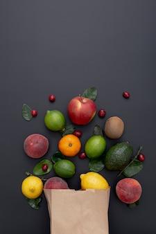 Vista superior de la variedad de frutas que salen de la bolsa de papel