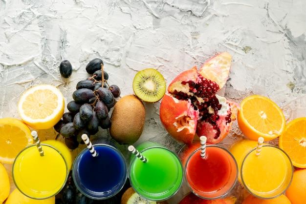 Vista superior de la variedad de jugo fresco, diferentes frutas alrededor, espacio de copia para su texto en una mesa negra