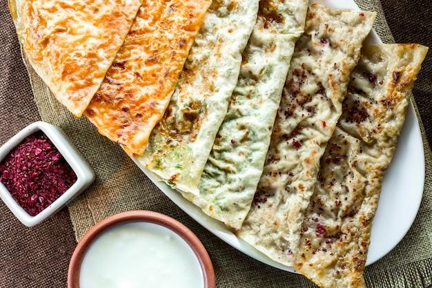 Vista superior de una variedad de kutabs con hierbas de calabaza y carne con yogur y zumaque