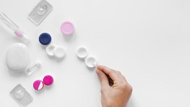 Vista superior variedad de lentes y accesorios con una mano