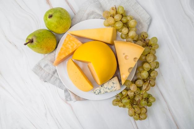Vista superior variedad de sabroso queso con uvas y peras