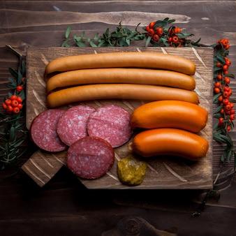 Vista superior de una variedad de salchichas con serbal y mostaza en utensilios de cocina
