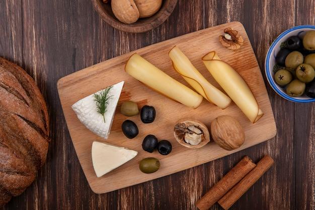 Vista superior de variedades de queso y aceitunas en un soporte con canela y hogazas de pan sobre un fondo de madera