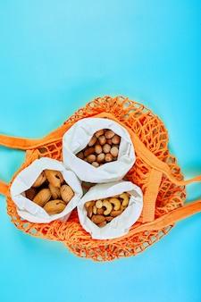 Vista superior de varios tipos de frutos secos sobre la mesa en una bolsa de papel en la bolsa de la compra sobre fondo azul, cero desperdicio de alimentos. vida libre de desperdicios, entrega de nueces. copie el espacio.