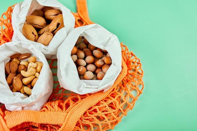 Vista superior de varios tipos de frutos secos sobre la mesa en una bolsa de papel en la bolsa de la compra sobre fondo verde, cero compras de residuos de alimentos. vida libre de desperdicios, entrega de nueces. copie el espacio.